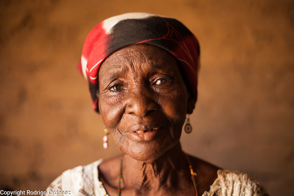 """Delou Ibrahim, 70, poses for a photograph at her home in Saran Maradi, Niger. <br /> Delou Ibrahim has four children and suffered the loss of nine. She has about 40 grandchildren, 16 of which live with her. <br /> """"I've seen several crises. The famine in 1984 was the hardest. Rains were very weak. The stems of millet came out but the spikes gave no grain - nothing,"""" she recalls. """"Two years ago at least there were people who harvested millet, but this year the crops have been worse because of the drought and the leaf miners."""" Delou's last crop was 30kg, which only provided food for about two days.<br /> Delou and her family receive cash from CARE. """"I get to buy cereal to feed my family, particularly my grandchildren."""" They have two daily meals, porridge in the morning and sorghum paste in the evening."""