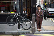 Chinese man wearing a Paisley outfit pattern on his trousers and shirt, in Hanbury Street near Brick Lane, London, UK. Fashion and style in this part of London is always interesting and often bizarre.