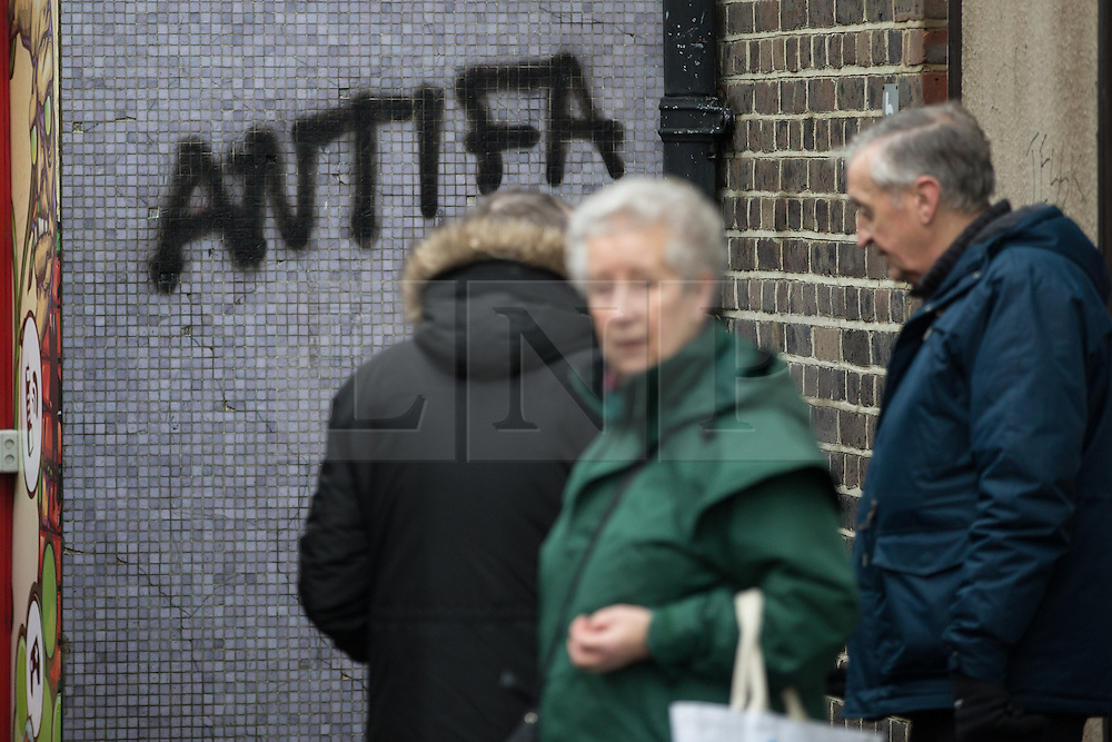 """© Licensed to London News Pictures . 30/01/2016 . Dover , UK . People queue at a bus stop next to anti-fascist graffiti reading """" ANTIFA """" ahead of demonstrations by far-right groups (including The National Front , The North West Infidels and The South East Alliance ) and , opposing them , anti-fascists , close to the port of Dover in Kent . Photo credit : Joel Goodman/LNP"""