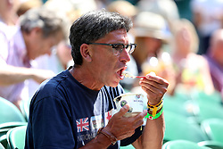 A spectator eats a tub of ice cream on day two of the Wimbledon Championships at the All England Lawn Tennis and Croquet Club, Wimbledon