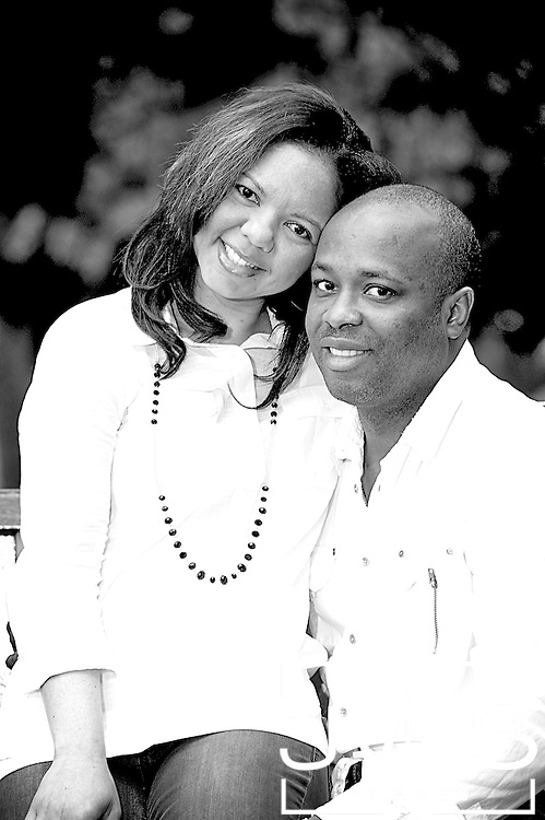 Engagement session in black and white with bride sitting her grooms lap and both smiling.
