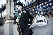 As the 45th US President is inaugurated in the USA, a mime artist dressed as Charlie Chaplin stands outside Parliament with a joke Trump cartoon fart in protest at the new President on 20th January 2017 in London, England, United Kingdom. President Donald Trump takes over as Commander in Chief on this day, and is one of the greatest upsets and shocks in political news history.
