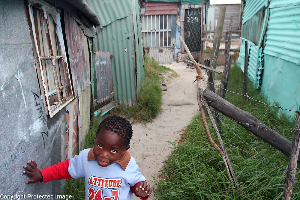 A young boys pauses near his family's shack in the Khayelitsha Township in Cape Town, South Africa.<br /> Photo by Shmuel Thaler <br /> shmuel_thaler@yahoo.com www.shmuelthaler.com