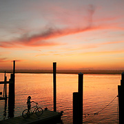 Wrightsville Beach, North Carolina - March 13: A woman stands with a bicycle on a dock at sunset in Wrightsville Beach, North Carolina, on March 13, 2007.