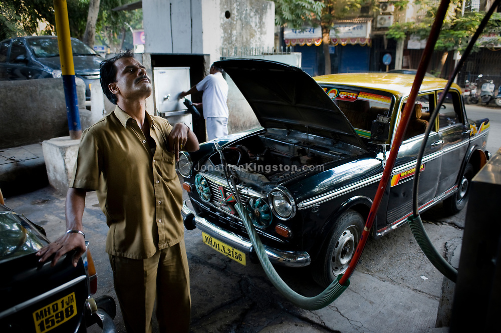 A taxi cab driver watches the price on the pump filling his cab with compressed natural gas in Mumbai, India. In 2006 the city of Mumbai mandated that all public transportation be run on Compressed Natural Gas or CNG.  This green shift has vastly improved air quality in the city of Mumbai.