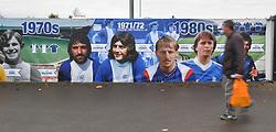 A fan walks past a timeline mural outside St Andrews, home of Birmingham City
