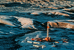 Aerial view of a frac operation at an oil rig site in the snow-covered Missouri Breaks of Montana.