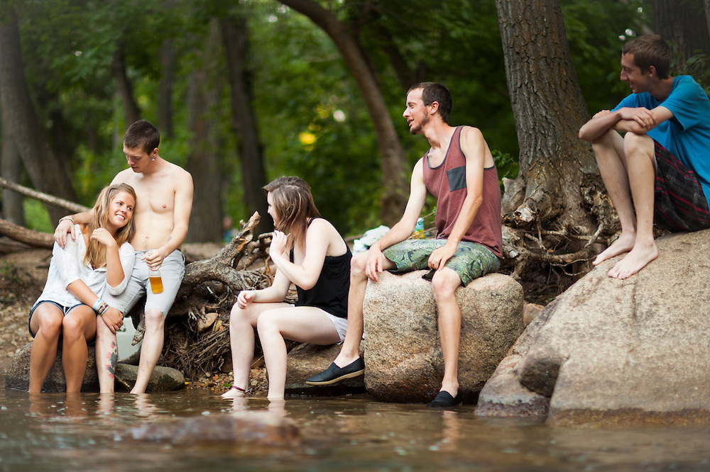 Friends hang out on the banks of Boulder Creek at Eben G. Fine Park on a hot summer day in Boulder, Colorado.