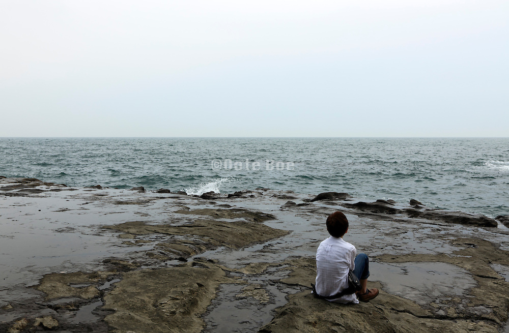 one person sitting and looking out over an empty sea