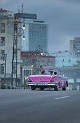 Vintage cars on Malecon city street under storm clouds, Havana, Cuba