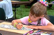 Girl age 4 coloring fish at Mississippi River Carp Festival.  Brooklyn Park  Minnesota USA