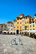 Bicycles in the Piazza dell'Anfiteatro inside the ancinet Roman ampitheatre of Lucca, Tunscany, Italy . Piazza dell'Anfiteatro is a public square in the northeast quadrant of walled center of Lucca. The ring of buildings surrounding the square, follows the elliptical shape of the former second century Roman amphitheater of Lucca. The square can be reached through four gateways located at the four vertices of the ellipse. A cross is carved into the central tile of the square with the arms pointing to the four gateways of the square. The base of the former amphitheater  dating back to the 1st or 2nd century BC, at its peak had about 18 rows of amphitheater seats held some 10,000 spectators.<br /> <br /> Visit our ITALY HISTORIC PLACES PHOTO COLLECTION for more   photos of Italy to download or buy as prints https://funkystock.photoshelter.com/gallery-collection/2b-Pictures-Images-of-Italy-Photos-of-Italian-Historic-Landmark-Sites/C0000qxA2zGFjd_k<br /> .<br /> <br /> Visit our ROMAN ART & HISTORIC SITES PHOTO COLLECTIONS for more photos to download or buy as wall art prints https://funkystock.photoshelter.com/gallery-collection/The-Romans-Art-Artefacts-Antiquities-Historic-Sites-Pictures-Images/C0000r2uLJJo9_s0 .<br /> <br /> If you prefer to buy from our ALAMY PHOTO LIBRARY  Collection visit : https://www.alamy.com/portfolio/paul-williams-funkystock/lucca.html .