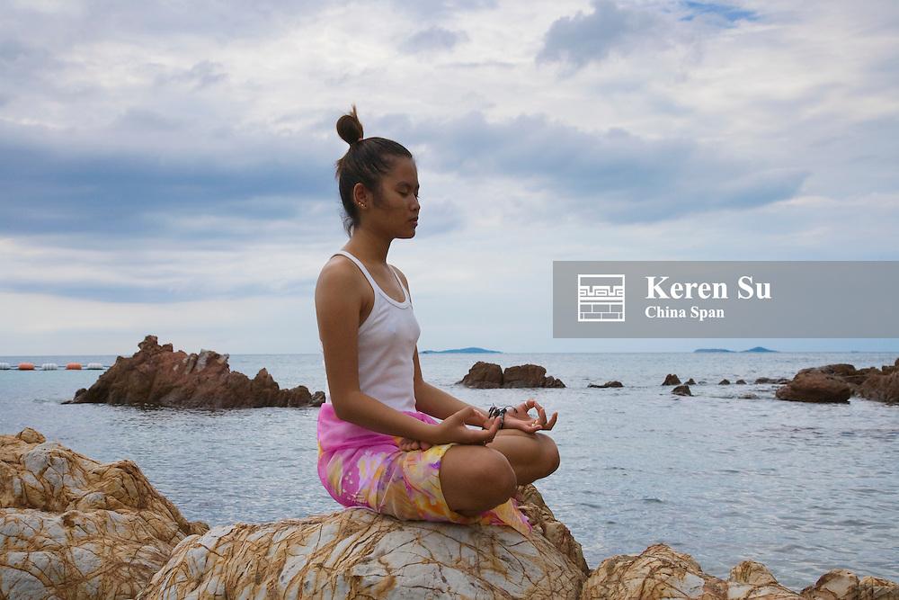 Girl practicing yoga on the beach, Long Island, Thailand