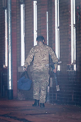 © Licensed to London News Pictures . 28/11/2013 . Manchester , UK . A man in army fatigues walks away from the house carrying a holdall and a metal frame . Scene at 17 Mellor Street in Eccles , Greater Manchester this evening (Thursday 28th November 2013) where police have cordoned off adjoining streets and evacuated houses following the discovery of a suspicious device .  Photo credit : Joel Goodman/LNP