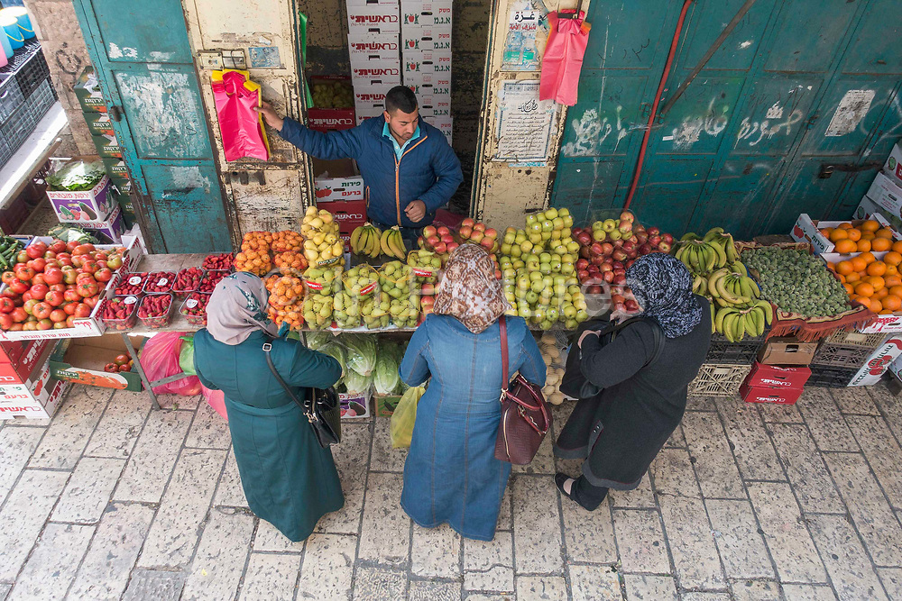 Three ladies shopping for fruit at a market stall next to Herods Gate in the Old City on 31st March 2016 in Jerusalem, West Bank.