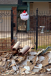 21st, December 2005. New Orleans Christmas decorations. A santa claus face hangs from a gate in front of a pile of rubble and debris cleared from a house in the devastated 9th ward following Hurricane Katrina.