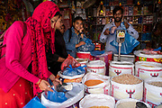 Women buying rice and pulses in a food shop along the main street through the centre of Besishahar on the 10th of March 2020, Besishahar, Lamjung District, Gandaki Pradesh, Nepal. Besishahar is a small town, municipality and the district headquarters of Lamjung District in Gandaki Pradesh, Nepal.