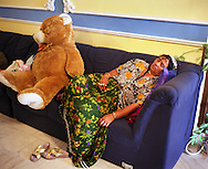 """Mother of Florin """"Ciprian' Lulu sleeps beside a large teddy bear on her sofa, in the run up to her 13 year old son's wedding, in the village of Sintesti, in Romania, early August 2006.  The Kalderari roma of Sintesti are by tradition metal workers, originally making alcohol stills, pots and pans, but now dealing in scrap metal. The large profits from their business have enabled them to build large houses in the village of Sintesti, 20km from Bucharest, and to invest in fast, Western brand name cars such as BMW's, Mercedes and Porsche."""