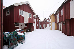 Red wooden buildings in traditional fishing village of Smogen during winter after snow on Bohuslan coast in Sweden