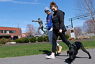 """Adam Simon, of Easton, and his girlfriend Molly Greig, right, of Easton, walk their 3-month old black Labrador retriever Hank on Mar. 21, 2020, through Scott Park in Easton, Pennsylvania. The couple takes several walks a day as they live in an apartment and know it's important to give the dog room to move. """"It's the only reason we leave the apartment,"""" Greig says, """"If we didn't have a puppy, we'd probably be inside right now."""" Communities across the Lehigh Valley are adjusting to life during the coronavirus pandemic that is impacting the daily lives of Pennsylvania residents both socially and economically. (Photo by Matt Smith)"""