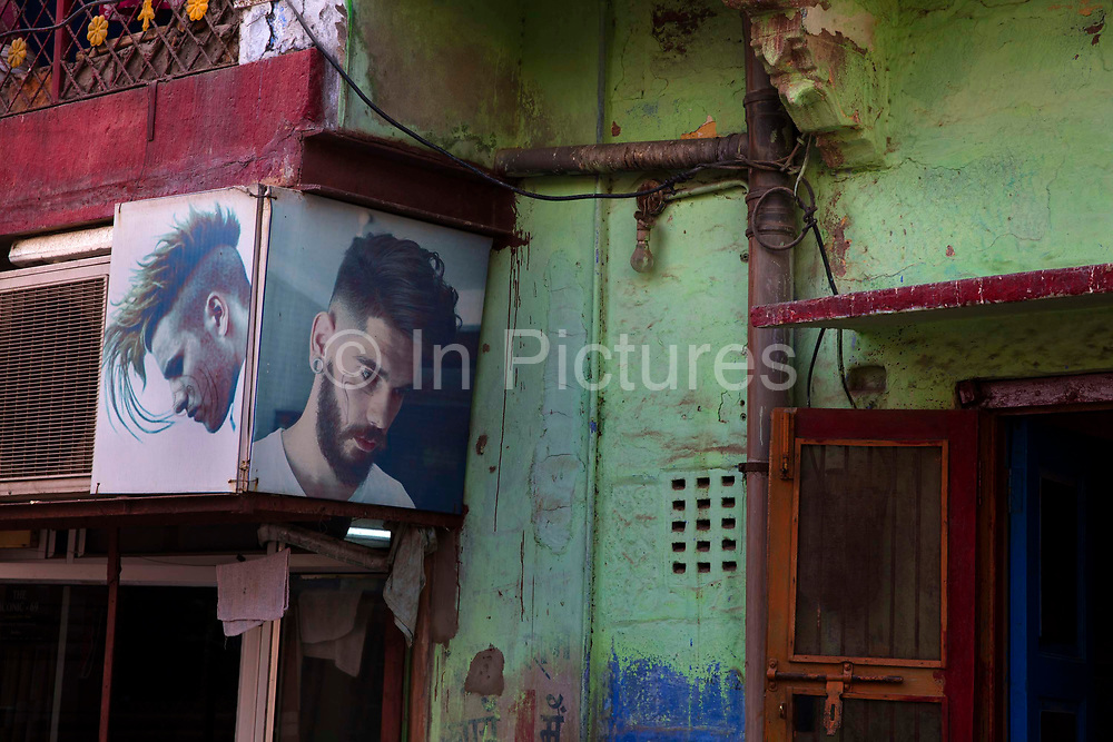 Barbers shop with trendy hairstyles in the city backstreets on 21st February 2018 in Jodhpur, Rajasthan, India. Popularly known as the Blue City, Jodhpur is a city in the Thar Desert of the northwest Indian state of Rajasthan.  Jodhpur is the Handicraft Hub of India.