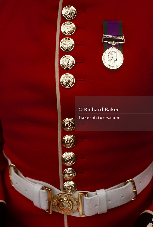 A detail of a Welsh Guard's red tunic uniform including a medal for service in Northern Ireland. Polished button and a faultlessly clean surface proves the high standards expected by this famous British army regiment. The Welsh Guards (Gwarchodlu Cymreig) part of the Guards Division, is one of the Foot Guards regiments of the British Army. The Welsh Guards came into existence on 26 February 1915 by Royal Warrant of His Majesty King George V in order to include Wales in the national component to the Foot Guards.
