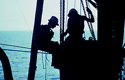 Silhouetted offshore oil rig workers.