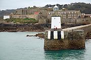 Lighthouse at harbour entrance with Castle Cornet behind, St Peter Port, Guernsey, Channel Islands, UK