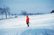 With a look of delight on her face, a four year-old girl stamps through fallen snow in a field near her home in Bielefeld, Germany. Wearing a vibrant red bobble hat and matching coat, she smiles towards the viewer with the pleasure of any child enjoying the excitement of fresh snow. Ski or sledge tracks can be seen at her feet but she is the only person in this empty landscape, as if she's walking on her own through the snowy hills. It is the winter of 1967 and the reds are very vibrant and dominant from the Kodachrome film used which also has a wonderful muted blue colour cast in the mid-tones giving the picture a chilly, wintry feel reminiscent of the classic days of early photography when shifts in color gave a faded and dated look.