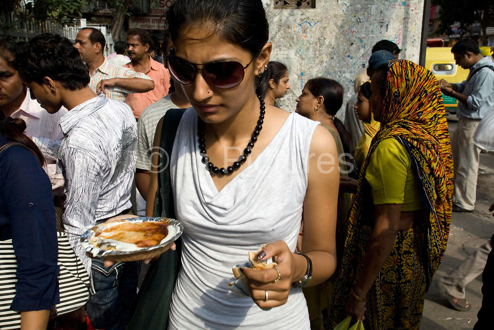 A woman eats a plate of street food walking through the streets of Chadni Chowk in Old Delhi, India