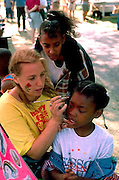 Face painter 23 with girls age 13 and 10 at Powderhorn Art Festival.  Minneapolis  Minnesota USA