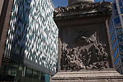 Modern architecture from nearby offices and the carving showing the disaster of the Great Fire of London at the base of the Monument, on 1st September 2016, in the City of London, England UK. This old landmark commemorates the Great Fire of 1666, a date sealed in the capitals history because it burned the central parts of the city of London, gutting the medieval area inside the old Roman city wall. It consumed 13,200 houses, 87 parish churches, St Pauls Cathedral and most of the buildings of the City authorities. It is estimated to have destroyed the homes of 70,000 of the Citys 80,000 inhabitants.