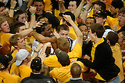 DeMarre Carroll, center, is embraced by teammate Keith Ramsey as fans storm the court after Missouri's 62-60 win over Kansas.