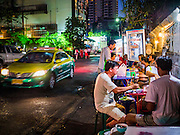 """30 MARCH 2013 - BANGKOK, THAILAND: A taxi drives past men eating at a street food stall in Bangkok. Thailand's economic expansion since the 1970 has dramatically reduced both the amount of poverty and the severity of poverty in Thailand. At the same time, the gap between the very rich in Thailand and the very poor has grown so that income disparity is greater now than it was in 1970. Thailand scores .42 on the """"Ginni Index"""" which measures income disparity on a scale of 0 (perfect income equality) to 1 (absolute inequality in which one person owns everything). Sweden has the best Ginni score (.23), Thailand's score is slightly better than the US score of .45.   PHOTO BY JACK KURTZ"""