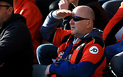 A Bournemouth fan shields his eyes from the sun in the stands