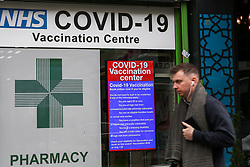 © Licensed to London News Pictures. 23/10/2021. London, UK. A man walks past the Covid-19 vaccination centre in north London. Ministers are urging people o get a Covid-19 vaccine and booster jab as the experts, have reported a low uptake amid fears of further restrictions this winter as coronavirus cases rise. The Government is considering cutting the interval between booster jabs and the second dose of a Covid-19 vaccine from six month to five months. Photo credit: Dinendra Haria/LNP