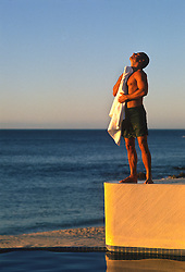 Sexy man toweling off while standing on a platform overlooking the Pacific Ocean in Mexico