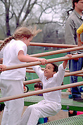 Kids age 10 climbing at the Powderhorn Park May Day Festival.  Minneapolis  Minnesota USA