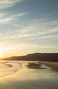 View of beach and sea with hills in background at sunrise, Bolonia, Andalusia, Spain