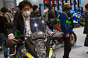 A Japanese man tries out sitting on a motorbike at the 44th annual Tokyo Motorcycle show. Tokyo Big Sight exhibition hall, Odaiba, Tokyo, Japan. Friday March 24th 2017. The show runs from Friday March 24th to Sunday March 26th and showcases technological innovations from all the main motorcycle manufacturers along with companies providing protective helmets pads and  clothing to decoration and even camping gear for bike-touring..