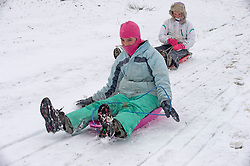 © Licensed to London News Pictures 07/02/2021.        Sevenoaks, UK. Two teenagers having fun sledging in the snow. Freezing cold snowy weather at Knole Park in Sevenoaks, Kent. Photo credit:Grant Falvey/LNP
