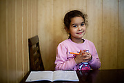 Sarlota Kroscen (6) is doing her homework for school in the kitchen of her parents. Visiting the family of Jitka Cervenakova (25) who is the mother of Sarlota (6) and Sebastian (4). Jitka is also a volunteer supporting other mothers with knowledge and explaining legal rights for getting their children into mainstream schools in the city of Ostrava, where Roma and non Roma children are educated together.