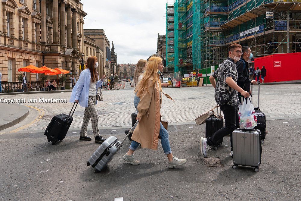 Edinburgh, Scotland, UK. 10 June 2021. With few overseas tourists in Edinburgh because of Coronavirus travel restrictions, many tourist shops on the Royal Mile are closed or suffering financial difficulties. Many have put signs in windows accusing the SNP Scottish Government of not doing enough to help save jobs. Pic; Group of Chinese people with suitcases on the Royal Mile. Iain Masterton/Alamy Live News