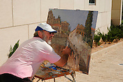 Artist at work with easel and palette and paint brush