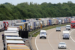 © Licensed to London News Pictures. 28/07/2015<br /> <br /> Operation stack lorries between J8 and J9 for Ashford on the M20. <br /> Operation stack is back on the M20 in Kent.<br /> Just days after Operation Stack was taken off the M20, it was brought back in the early hours of this morning.<br /> The authorities are blaming a heavy volume of traffic heading towards the Port of Dover and Eurotunnel and the continued disruption in Calais.<br /> The coast-bound carriageway between junctions 8 and 9 is closed to allow lorries to park, but the slip roads at junctions 9, 10 and 12 and 13 have also been shut. <br /> <br /> (Byline:Grant Falvey/LNP)
