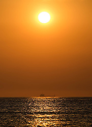 © Licensed to London News Pictures.02/07/15<br /> Saltburn by the Sea, UK. <br /> <br /> A container ship heads along the North Yorkshire coastline as the sun climbs higher in the morning sky.<br /> <br /> Photo credit : Ian Forsyth/LNP