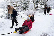 Local people out and about enjoying the snow, pulling one another along on sledges in Kings Heath Park on 24th January 2021 in Birmingham, United Kingdom. Deep snow arrived in the Midlands giving some light relief and fun during the current lockdown for people who simply enjoyed the weather.