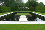 A modern, minimalist pool garden with raised, apparently 'floating' steps and grass platform. <br /> <br /> At the far end of the pool is a striking, tall copper water feature consisting of 24 stylized waterlily leaves. Water fed up the stems emerges across the leaves to drip off as a series of delicate droplets.<br /> <br /> Date taken: 14 June 2010.
