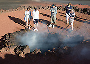 Tourists stand around fire in small crater, Parque Nacional de Timanfaya, national park, Lanzarote, Canary Islands,