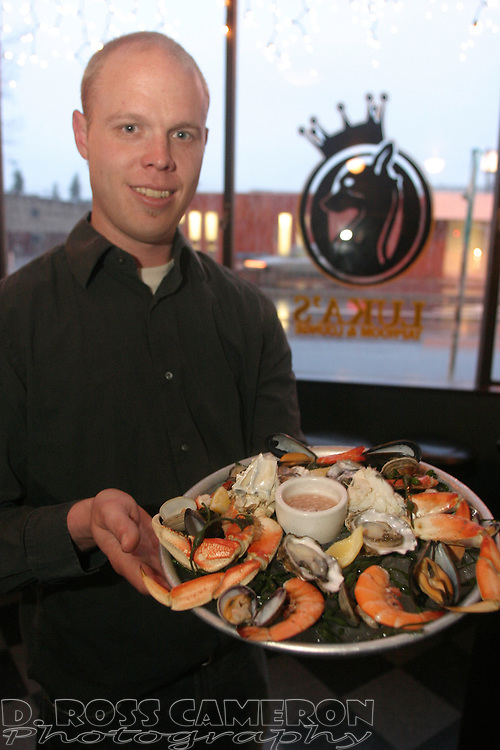 Byron Schostag, manager of Luka's Taproom and Lounge, shows off a West Grand Plateau, a platter of oysters, mussels, clams, prawns and dungeness crab, Monday, March 21, 2005 in Oakland, Calif. (Photo by D. Ross Cameron)